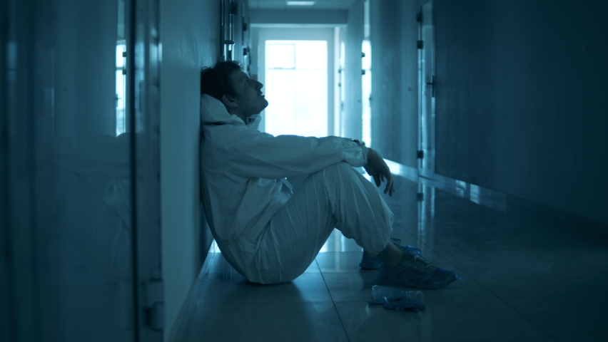 Tired paramedic is having a break on the floor in the hall Royalty-Free Stock Footage #1059188645