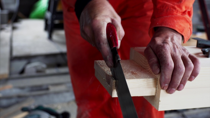 Close view of unidentified carpenter's hands who is cutting a wooden plank with a small manual saw. Carpenter workshop | Shutterstock HD Video #1059188912