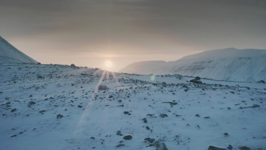 Aerial view of snowy mountains in Norway Spitzbergen. Sun rays on horizon. Background nature video. | Shutterstock HD Video #1059189686