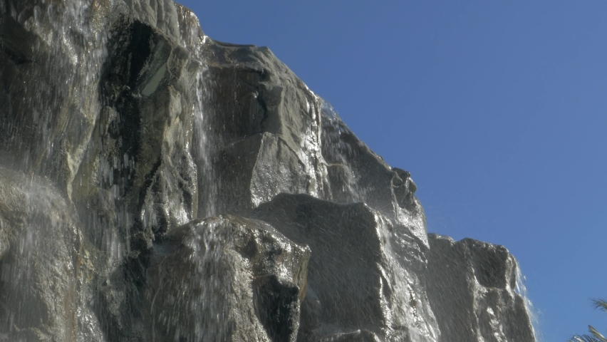 Small waterfall. Water splashes down a cliff against a blue sky, many separate streams flow down the rocks and break into splashes   Shutterstock HD Video #1059192098
