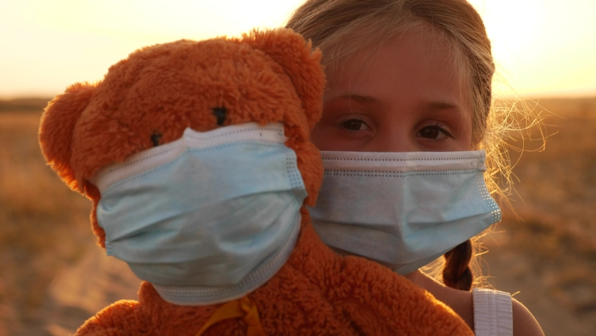 child girl in medical protective mask holding a teddy bear at sunset. concept pandemic coronavirus. covid -19 girl kid face in a medical mask with a teddy bear toy. girl during coronavirus quarantine Royalty-Free Stock Footage #1059192554