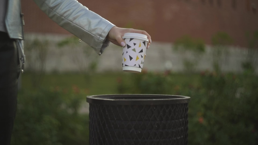 Girl metal jacket park center city holds her hand empty cup coffee colorful patterns on trash can street. Throws used mug into trash can. Environmental protection. Bio technology. Waste sorting.   Shutterstock HD Video #1059193355