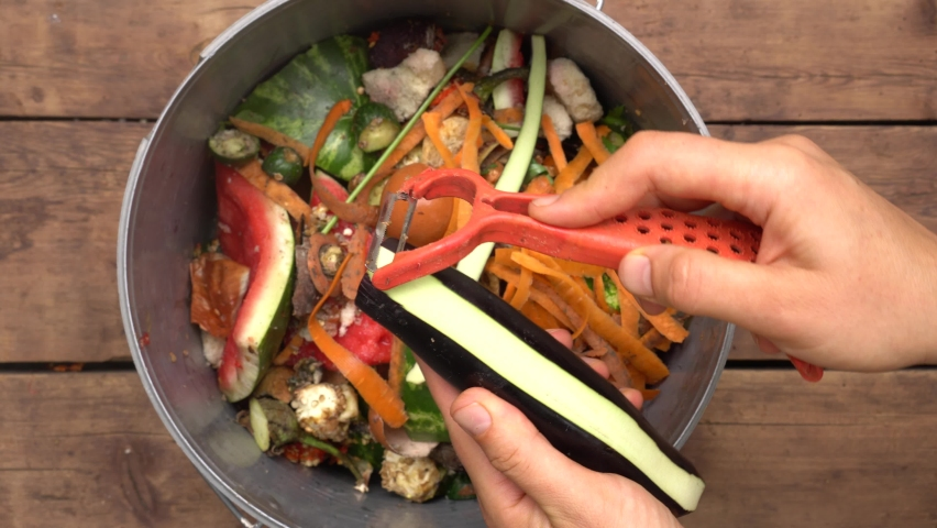 Reduce food loss and waste. Housewife throws vegetable peeling, scraps and fruit peels in compost bucket. Top view. Organic kitchen home waste gathering for composting   Shutterstock HD Video #1059195119
