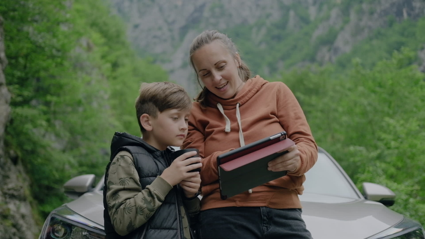 Mother and her son travelers drinking hot tea  and looking at tablet during a car summer trip in Montenegro.
