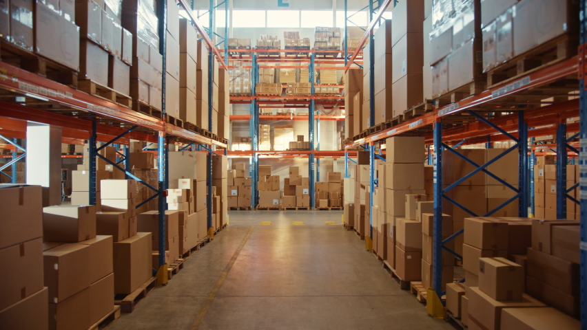 Big Retail Warehouse full of Shelves with Goods in Cardboard Boxes and Packages. Logistics, Sorting and Distribution Facility for Product Delivery. High Moving Backward Between Rows of Shelves Camera Royalty-Free Stock Footage #1059197549
