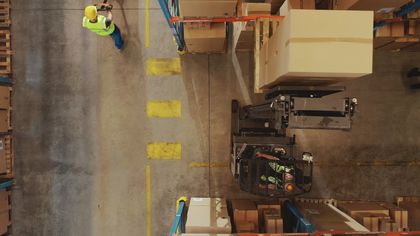 Top-Down Aerial Drone Shot: Electric Forklift Truck Operator Lifts Pallet with Cardboard Box of in a Big Retail Warehouse a Shelf. Logistics Product and Goods Delivery and Distribution Center