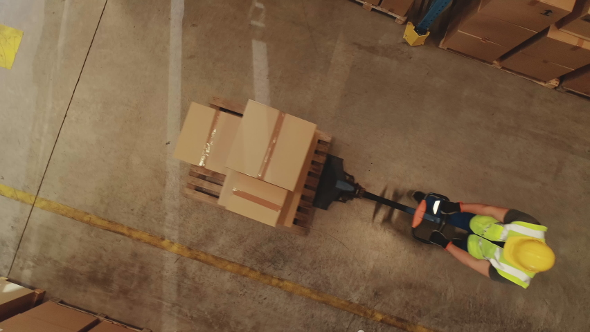 Top-Down Elevating View: Worker Moves Cardboard Boxes using Hand Pallet Truck, Walking between Rows of Shelves with Goods in Retail Warehouse. People Work in Product Distribution Logistics Center