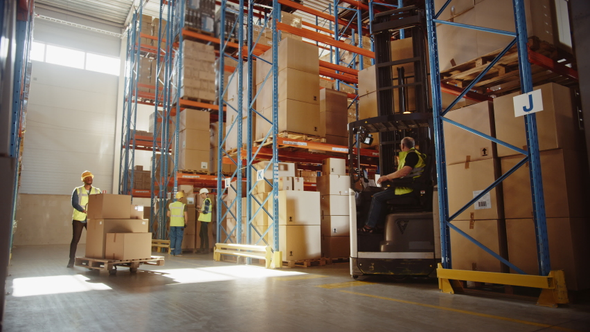 Retail Warehouse full of Shelves with Goods: Electric Forklift Truck Operator Lifts Pallet with Cardboard Box on a Shelf. People Working, Scanning Products, Using Trucks in Logistics Delivery Center Royalty-Free Stock Footage #1059197738
