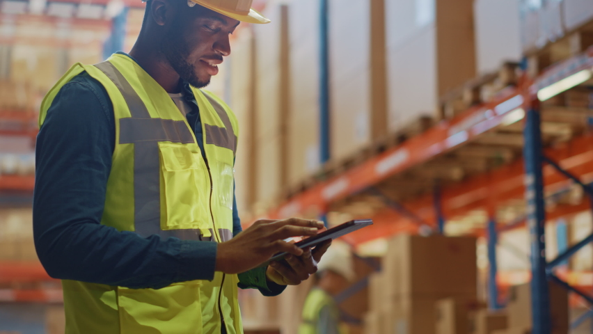 Male Worker Wearing Hard Hat Checks Products Stock and Inventory with Digital Tablet Standing in Retail Warehouse full of Shelves with Goods. Arc Shot Moves to People Operating Forklifts and Trucks | Shutterstock HD Video #1059197798