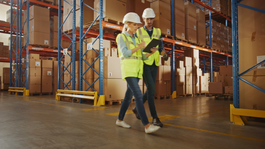 Retail Delivery Warehouse full of Shelves with Goods in Cardboard Boxes, Workers Scan and Sort Packages, Move Inventory with Pallet Trucks and Forklifts. Product Distribution and Delivery Logistics. | Shutterstock HD Video #1059197858