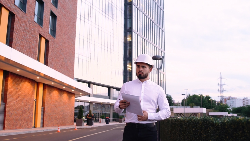 Walking frame with a handsome engineer wearing a helmet and holding a business plan. The engineer analyzes the works and makes notes in his notebook. | Shutterstock HD Video #1059198212
