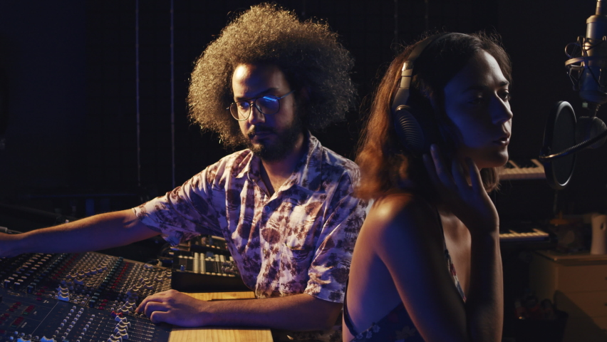 Music studio. Creative people. Hispanic man and woman working in the recording studio. Brunette curly couple is producing songs in comfortable environment. Royalty-Free Stock Footage #1059199217