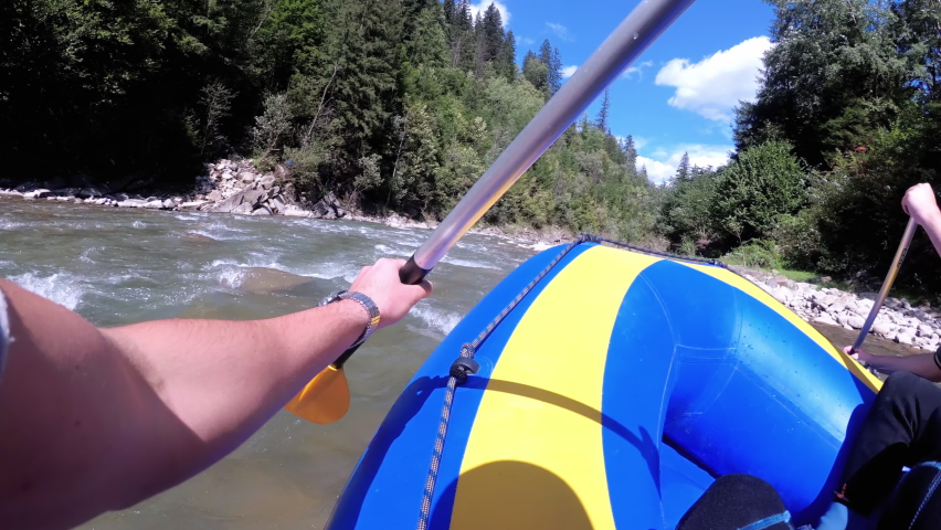 Rafting in the First Person on a Rough Mountain River. Extreme POV of the paddle and boat in motion. White Water Rafting on Rough Water. People Descending Raging Rapids from Whitewater. Chest View. | Shutterstock HD Video #1059201536