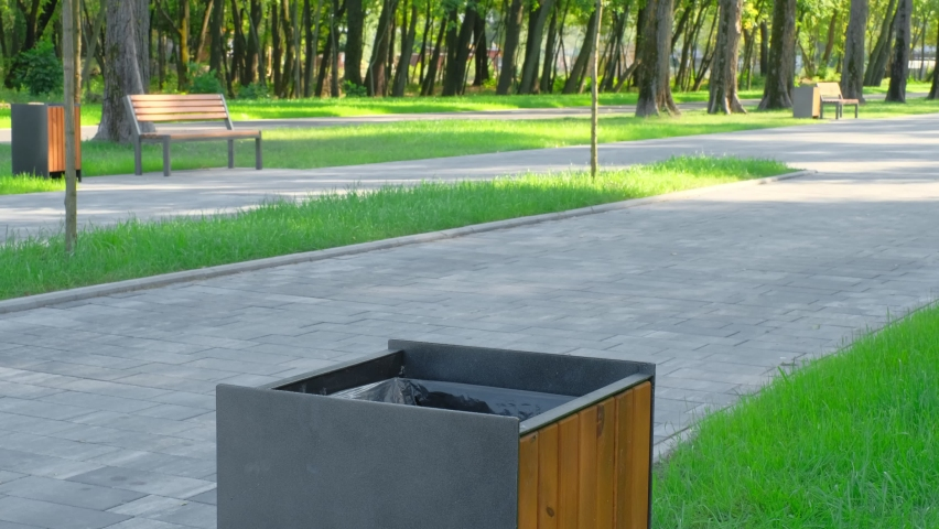 Public park cleaning on a sunny day. A young man throws out a garbage bag. Environmental problems. Cleanliness of the environment   Shutterstock HD Video #1059206156