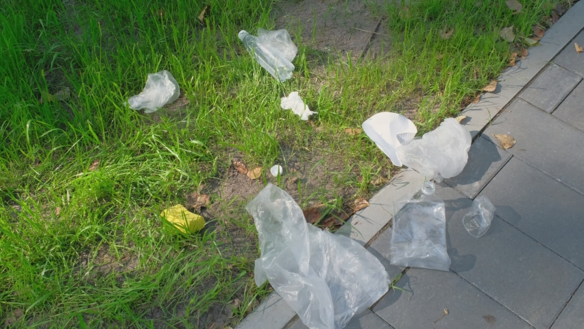 Garbage from plastic bottles, bags, paper in the park area. Public park cleaning. Environmental protection concept   Shutterstock HD Video #1059206270