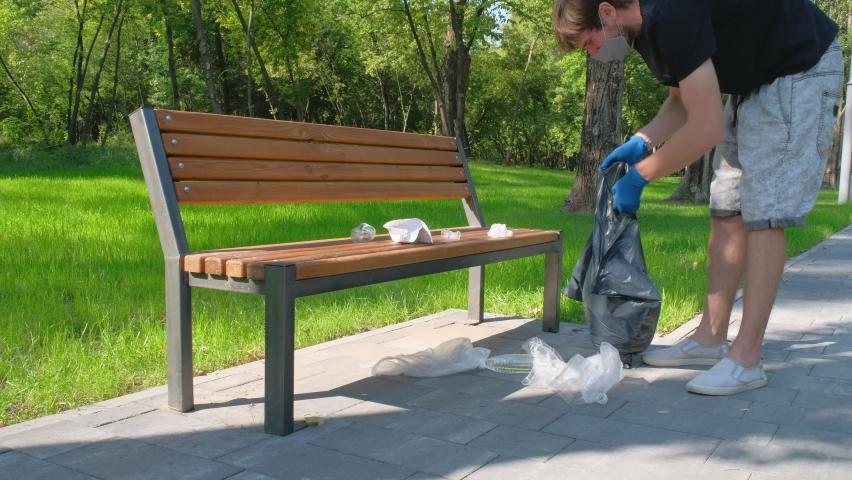 A male volunteer in rubber gloves collects garbage and household waste in a bag in a park along the road. Environmental problems. Environmental protection concept.   Shutterstock HD Video #1059206282