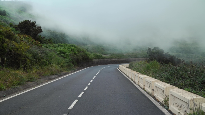 First-person view of motion along a mountain road at cloud level, slopes covered with green vegetation and high humidity. Canary Islands, Spain. | Shutterstock HD Video #1059207395