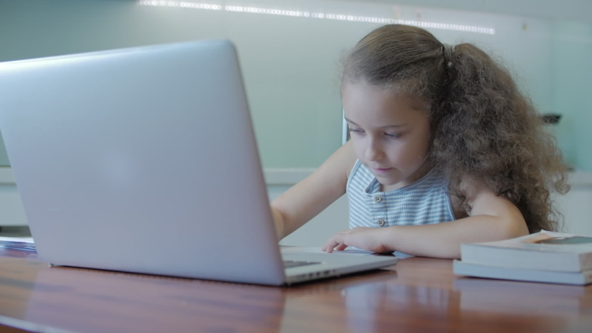 Little girl a cute elementary school child of 7-8 years old at home studying in family learning listens to school lectures does homework without leaving home.Child homeschooling,kids education concept
