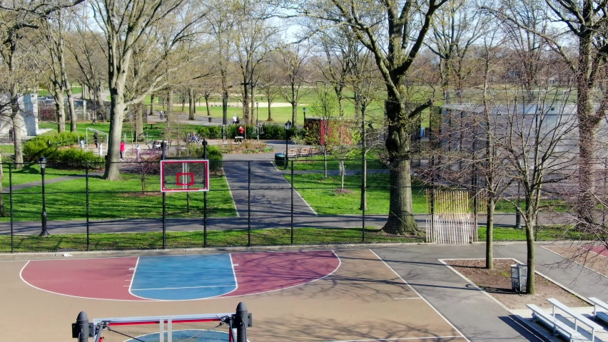 An empty basketball court with rims removed during Covid-19 at Marine Park in Brooklyn, New York.  Removing the rims ensures that no one will play in close proximity of each other. | Shutterstock HD Video #1059211175