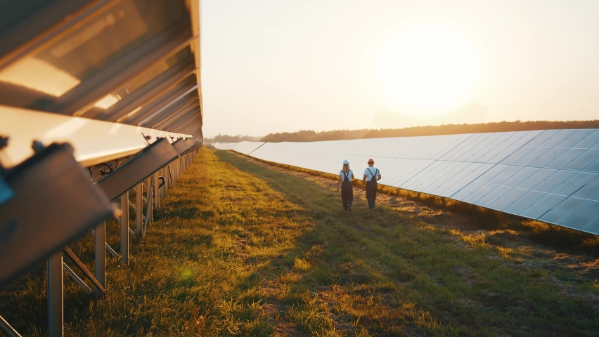 Photovoltaic field producing solar energy. Couple of workers examining solar batteries and communicating on business walking between rows. Ecological future. Royalty-Free Stock Footage #1059211295