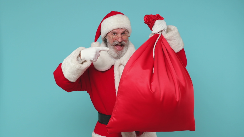 Santa Claus man in Christmas hat red suit coat white gloves glasses hold big sack bag with presents showing thumbs up isolated on blue color background studio. Happy New Year celebration merry holiday | Shutterstock HD Video #1059211379