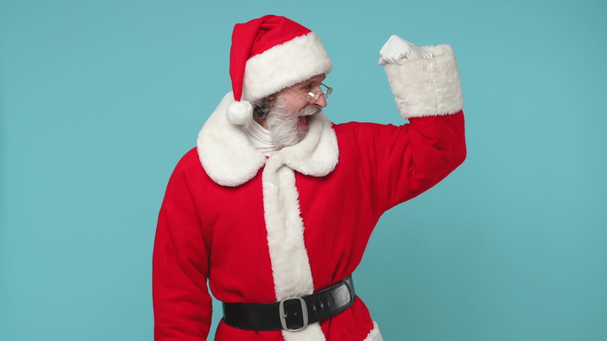 Strong fun elderly Santa Claus man in Christmas hat red suit coat white gloves glasses showing biceps muscles isolated on blue color background studio. Happy New Year celebration merry holiday concept   Shutterstock HD Video #1059211484
