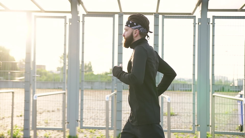 Good-looking confident sportive hardworking 35-aged bearded runner in black headband and sportswear which doing jog cardio exercises on the modern stadium   Shutterstock HD Video #1059213185