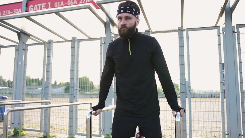 Portrait of good-looking purposeful confident young bearded athlete in black headband and sports clothes which doing strenghing exercises on handrails   Shutterstock HD Video #1059213188