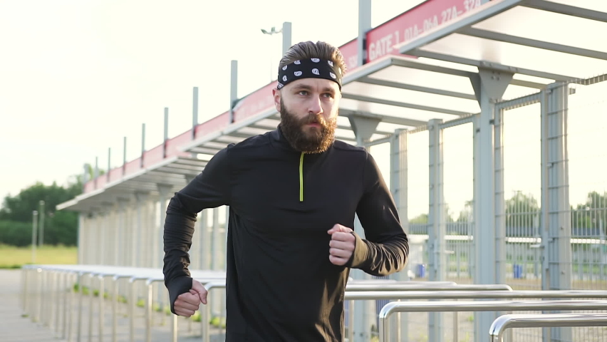 Marathon distance concept where handsome confident sporty strong 35-aged bearded runner doing jog cardio exercises on the modern stadium   Shutterstock HD Video #1059213191