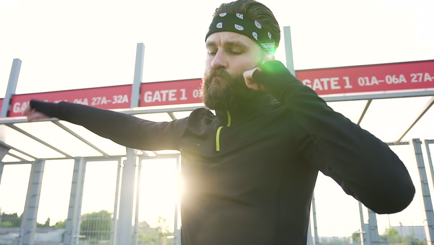 Portrait of good-looking balanced 35-aged confident bearded sportsman in black-white headband and black sports clothes which doing different exercises for his arms and legs in front of stadium's   Shutterstock HD Video #1059213194