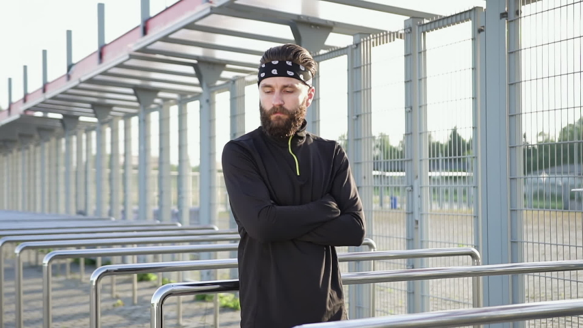 Front view of good-looking concentrated 35-aged sporty bearded athlete in black-white headband and black sports clothes which posing on camera near modern stadium   Shutterstock HD Video #1059213197