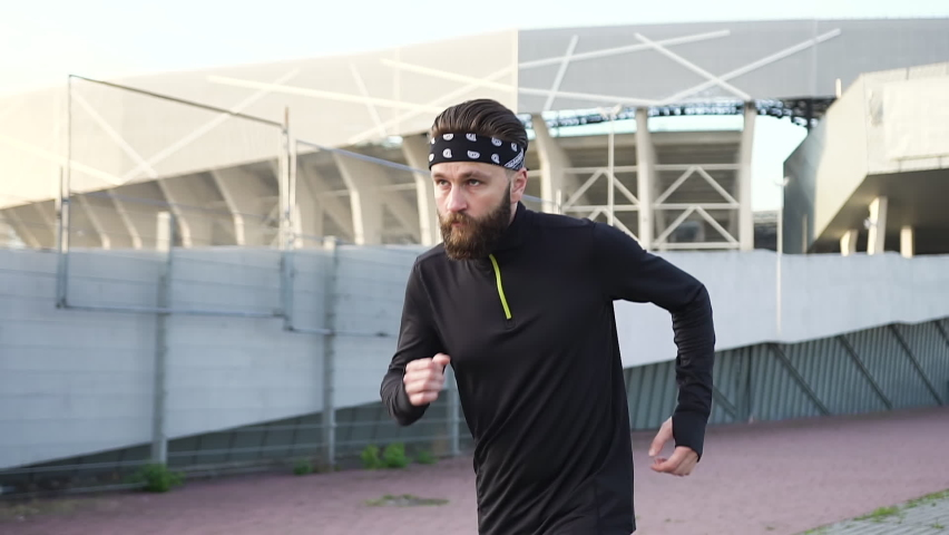 Portrait of handsome confident active strong 35-aged bearded sportsman in black-white headband and black sports clothes which doing jog cardio exercises on well-equipped stadium   Shutterstock HD Video #1059213200