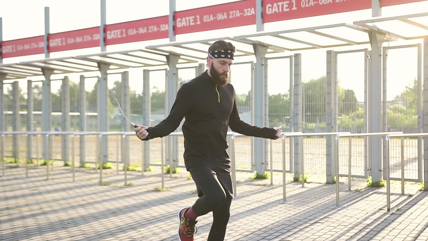 Good-looking confident hardworking 35-aged bearded sportsman with black headband and clothes jumping using skipping rope on modern sportsground   Shutterstock HD Video #1059213206