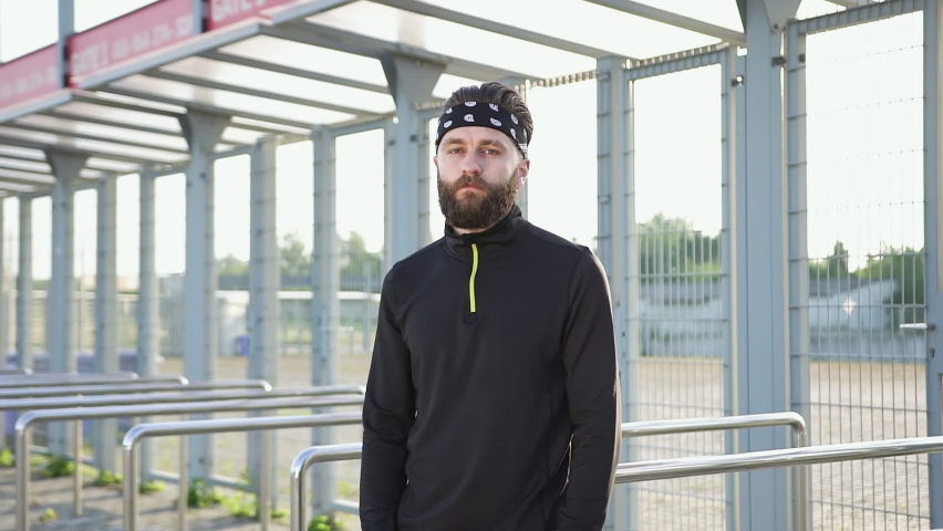 Close up of good-looking concentrated purposeful adult active male sportsman with well-groomed beard in headband and black sports clothes posing on camera in front of outdoors sportsground   Shutterstock HD Video #1059213212