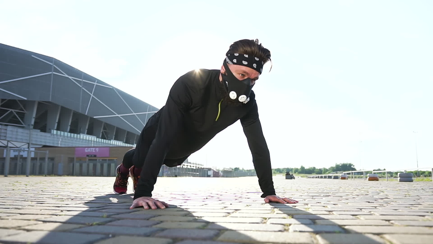 Portrait of good-looking strong sporty bearded guy in black protective mask in black-white headband and black sports clothes which doing push-ups during outdoors workout ,covid-19 concept   Shutterstock HD Video #1059213272
