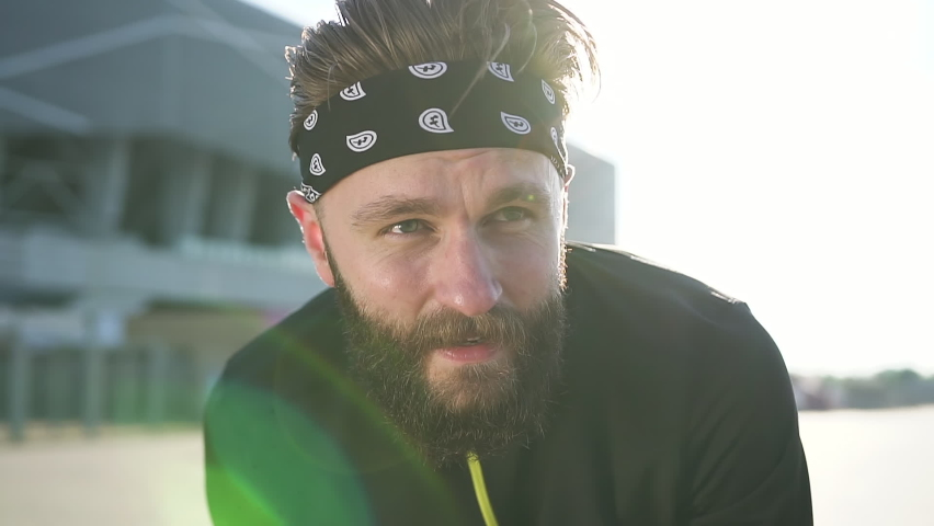 Likable tired sporty hardworking bearded guy in black-white headband and black training clothes resting after outdoors workout on big city stadium,close view   Shutterstock HD Video #1059213278