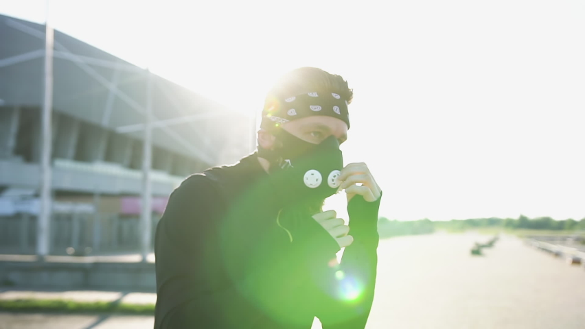 Good-looking sporty confident male sportsman in black mask and headband and sports clothes practicing different boxing punches outdoors in the light of sunbeams,slow motion   Shutterstock HD Video #1059213287