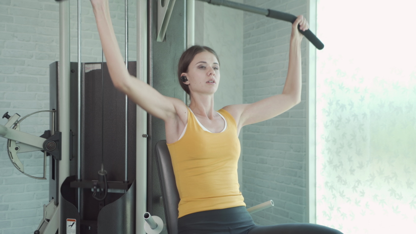 Portrait of fit white healthy woman, caucasian person, doing exercise, working out, and training in gym or fitness center in sport and recreation concept. Lifestyle activity.   Shutterstock HD Video #1059213656