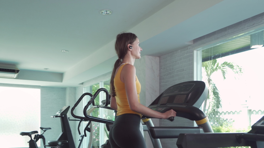 Portrait of fit white healthy woman, caucasian person, running or jogging on treadmill, and training in gym or fitness center in sport and recreation concept. Lifestyle activity.   Shutterstock HD Video #1059213662