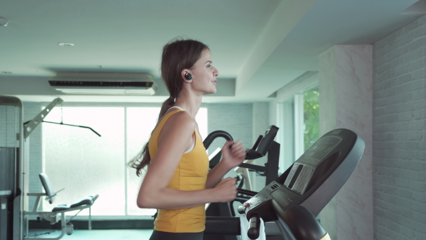 Portrait of fit white healthy woman, caucasian person, running or jogging on treadmill, and training in gym or fitness center in sport and recreation concept. Lifestyle activity.   Shutterstock HD Video #1059213665