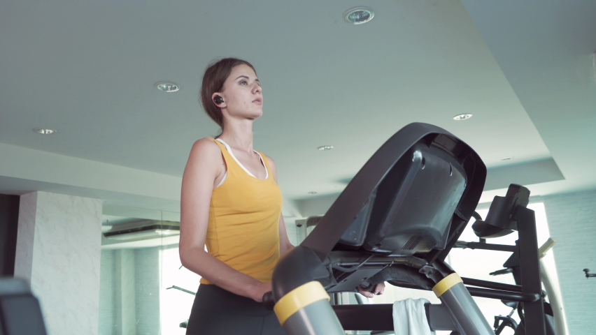 Portrait of fit white healthy woman, caucasian person, running or jogging on treadmill, and training in gym or fitness center in sport and recreation concept. Lifestyle activity.   Shutterstock HD Video #1059213668