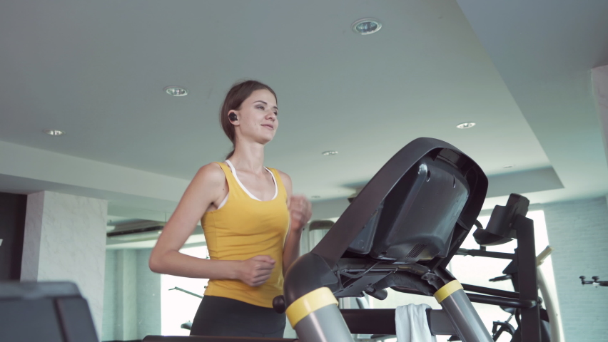Portrait of fit white healthy woman, caucasian person, running or jogging on treadmill, and training in gym or fitness center in sport and recreation concept. Lifestyle activity.   Shutterstock HD Video #1059213671