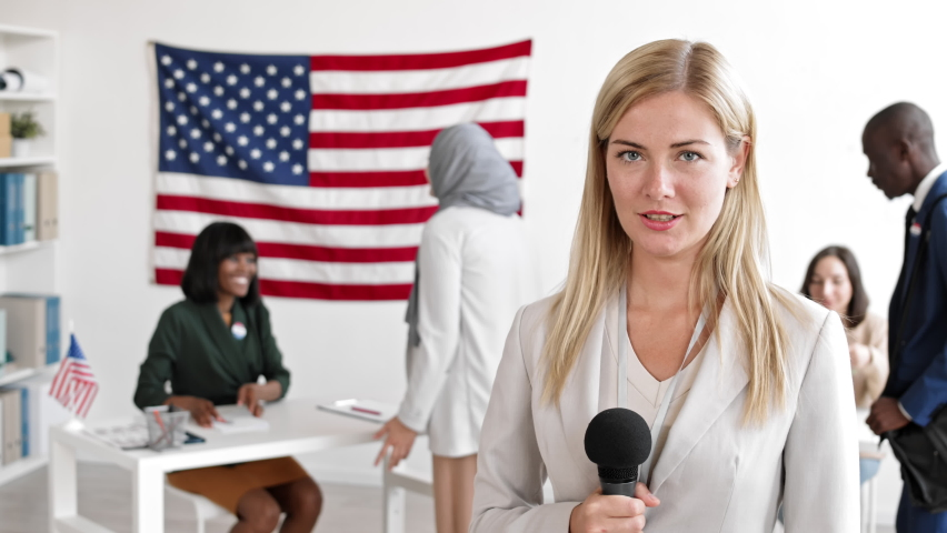 Medium shot of female Caucasian reporter with microphone in hand standing in the voting station where multiethnic citizens electing future USA president and making a report