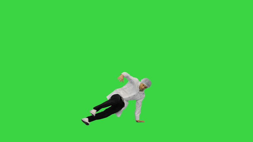 Male doctor in white robe and protective cap dancing breakdance on his head and arms on a Green Screen, Chroma Key.