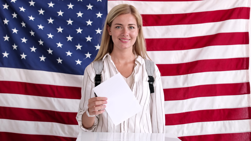 Medium shot of attractive Caucasian woman with blond hair is standing against USA flag, putting bulletin into ballot box and going away