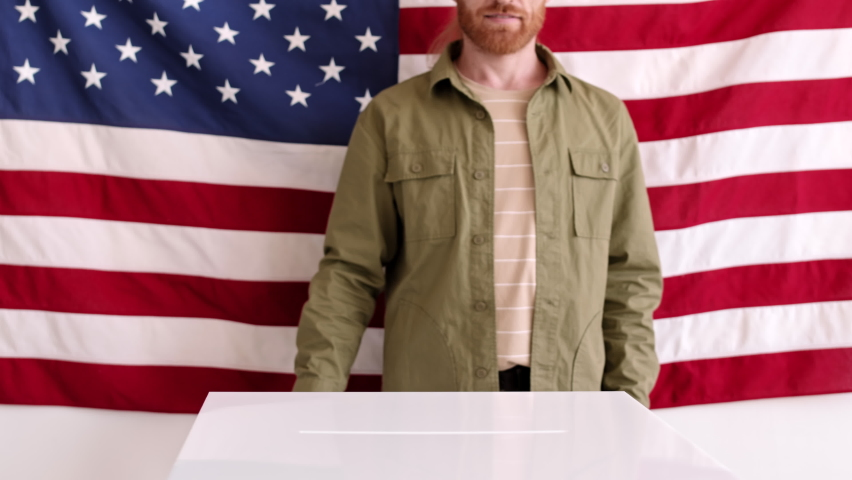 Lockdown of Caucasian man with ginger beard is standing against big USA flag, putting bulletin into ballot box and going away
