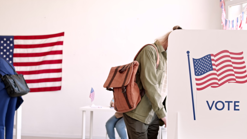 Medium shot of middle-aged Caucasian man wearing casual clothes and medical mask going out of voting booth with bulletin in hands and looking at camera while other people keep voting