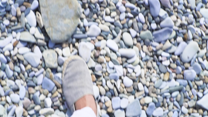 Close-up of men's feet walking on stone beach. Media. Top view of stylish legs of man walking on stone beach. First-person gait of man | Shutterstock HD Video #1059217529