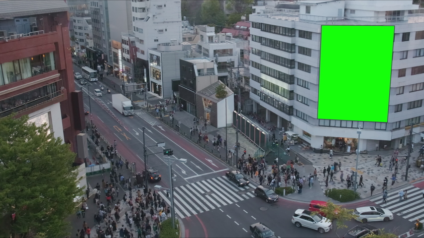 Large billboard with a green screen for advertising, on the modern building, busy crossroad with neon lights, traffic, crowd, Tokyo, Japan.  | Shutterstock HD Video #1059217865
