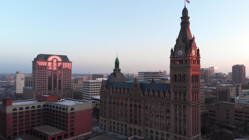 Establishing shot of Downtown Milwaukee, Wisconsin at sunrise. Aerial view of American city skyline  at dawn. United States of America Flag waving on the top of the tower